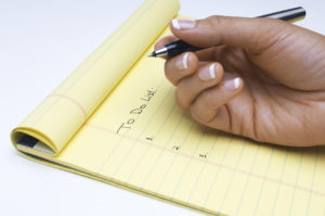 Woman writing list of tasks to do, close-up of hand